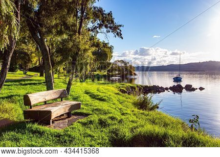 Comfortable wooden bench. The largest Lake Taupo in New Zealand. The magnificent lake is a popular holiday destination for tourists. Warm evening on the lake. Magnificent sunset.
