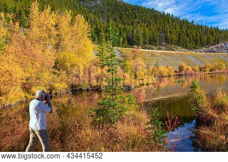 Gray-haired man photographs a beautiful landscape. Indian summer in the Rocky Mountains. Yellow autumn grass on the shores of mountain lake Vermillon. Canada