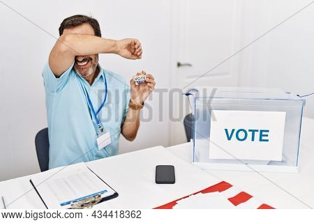 Middle age man with beard sitting by ballot holding i vote badge smiling cheerful playing peek a boo with hands showing face. surprised and exited