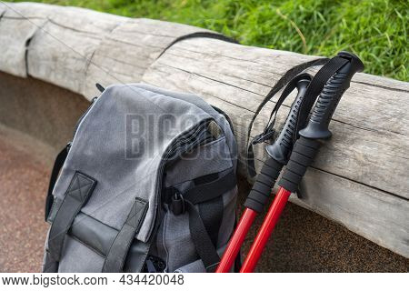 Nordic Walking Sticks Lie Next To The Backpack. Hiking, Tourism, Nordic Walking Concept.