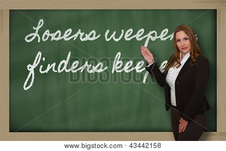 Teacher Showing Losers Weepers, Finders Keepers On Blackboard