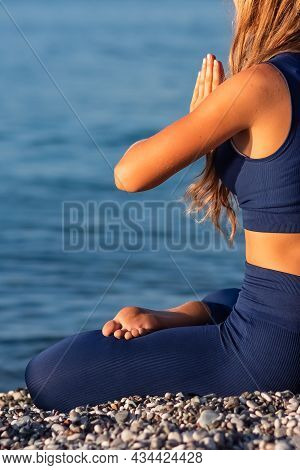 Young Girl Sitting In Lotus Pose On The Beach At Sunset.