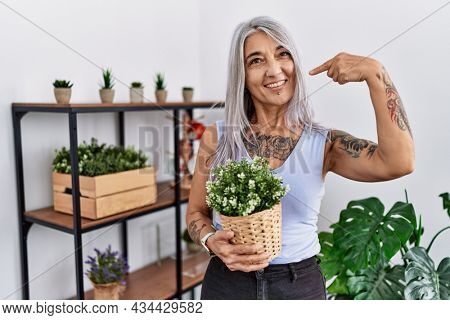 Middle age grey-haired woman holding green plant pot at home smiling cheerful showing and pointing with fingers teeth and mouth. dental health concept.