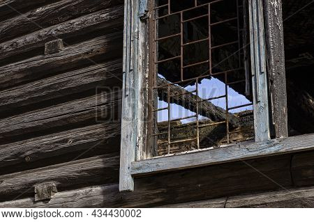 A Window With A Grate In An Old Abandoned Log House After A Fire, A Burned Down House.
