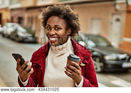 Beautiful business african american woman with afro hair smiling happy and confident outdoors at the city using smarpthone