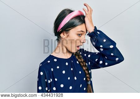 Young brunette girl wearing elegant look surprised with hand on head for mistake, remember error. forgot, bad memory concept.