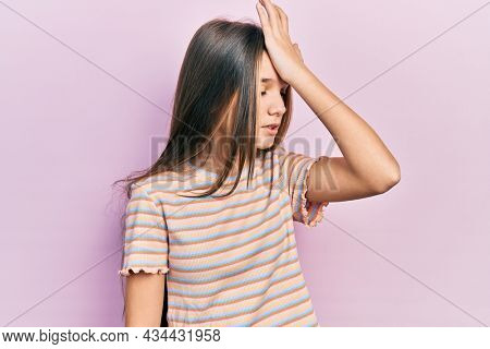 Young brunette girl wearing casual striped t shirt surprised with hand on head for mistake, remember error. forgot, bad memory concept.
