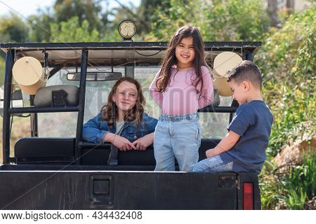 Smiling Children Having Fun In The Back Of Their Pickup Truck Enjoying The Road Trip In Country Side