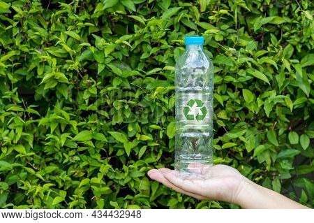 Bottle Of Fresh Water On Green Tree Wall. Hand Holding Plastic Water Bottle In Concept Recycle Save