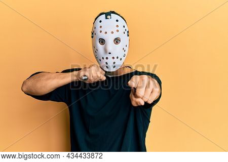 Man wearing hockey mask holding butcher knife looking dangerous and threatening