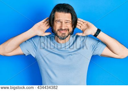 Middle age caucasian man wearing casual clothes trying to hear both hands on ear gesture, curious for gossip. hearing problem, deaf