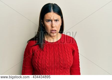 Beautiful brunette woman wearing wool winter sweater skeptic and nervous, frowning upset because of problem. negative person.