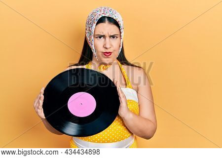 Young hispanic woman wearing pin up style holding vinyl disc skeptic and nervous, frowning upset because of problem. negative person.