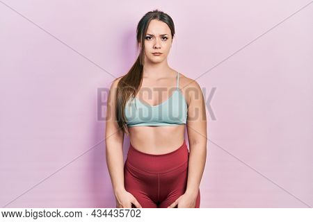 Young hispanic girl wearing sportswear skeptic and nervous, frowning upset because of problem. negative person.