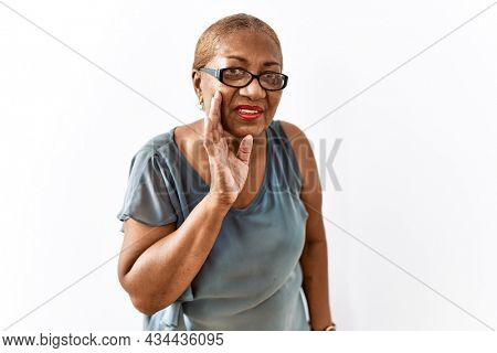 Mature hispanic woman wearing glasses standing over isolated background hand on mouth telling secret rumor, whispering malicious talk conversation