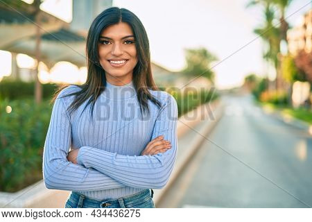 Beautiful hispanic woman smiling confient with crossed arms at the city