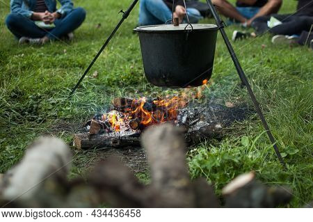 Dark Big Pot Or Cauldron, Cooking Pan With Boiling Water Inside Above The Fire Somewhere In The Park