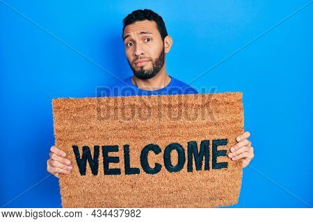 Hispanic man with beard holding welcome doormat clueless and confused expression. doubt concept.