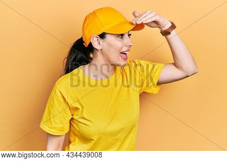 Young hispanic woman wearing delivery uniform and cap very happy and smiling looking far away with hand over head. searching concept.