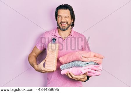 Middle age caucasian man holding laundry clothes and detergent bottle winking looking at the camera with sexy expression, cheerful and happy face.