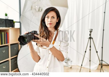 Beautiful caucasian woman working as photographer at photography studio relaxed with serious expression on face. simple and natural looking at the camera.