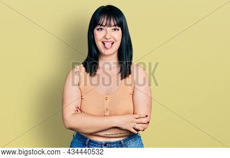 Young hispanic plus size woman with arms crossed gesture sticking tongue out happy with funny expression.