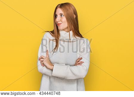 Young irish woman wearing casual winter sweater looking to the side with arms crossed convinced and confident