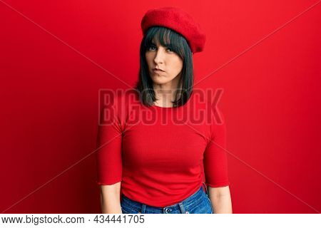 Young hispanic woman wearing french look with beret skeptic and nervous, frowning upset because of problem. negative person.