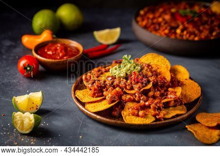 Delicious Plate Of Yellow Corn Nachos Chips With Cheese, Minced Meat And Red Hot Salsa Over Dark Bac