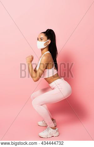 Young Sportswoman In Medical Mask Doing Squat Exercise On Pink