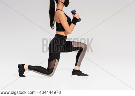 Cropped View Of Sportswoman In Black Protective Mask Exercising With Dumbbells On Grey