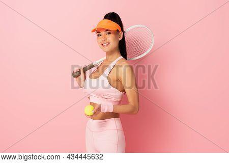 Joyful Sportswoman In Tennis Cap Holding Racket And Ball On Pink