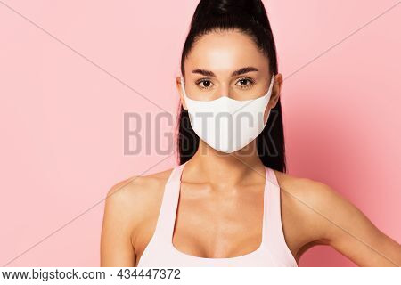 Young Sportswoman In Medical Mask Looking At Camera On Pink