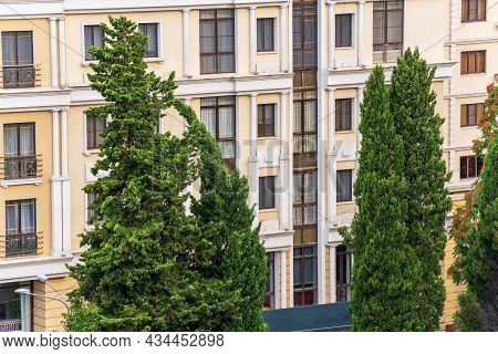 Two Tall Green Cypresses On The Background Of A Fragment Of The Facade Of A Residential Building Wit