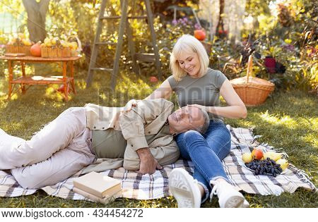 Tender Senior Couple Enjoying Time Together, Resting On Picnic Blanket In Garden And Chatting, Man L