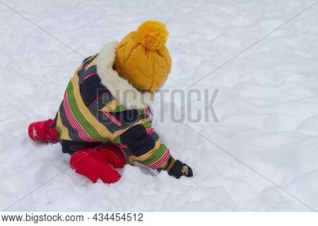 A Little Girl In A Winter Jumpsuit Plays In The Snow In Winter And Makes A Snowman Out Of Snow.