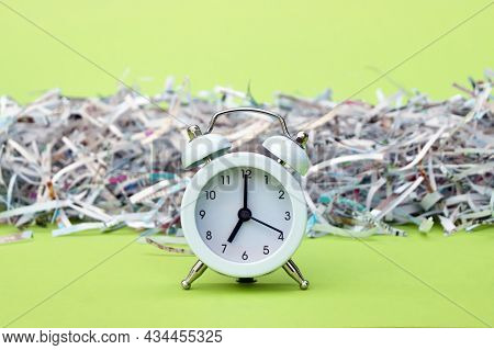 A White Vintage Clock In The Foreground Of 7:00 Am On A Light Green Background. Shredded Paper In Th