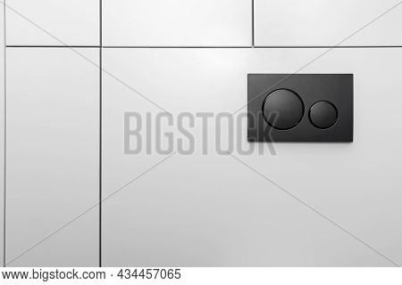 Black Matt Toilet Flush With Two Round Buttons Placed In The Wall Of A Restroom Lined With A Wooden