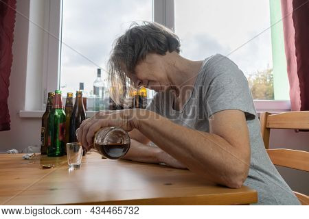 Old Senior Female Woman Sit Next To Table Drink Alcohol Bottle At Home Sad Alone Alcoholism Signs An