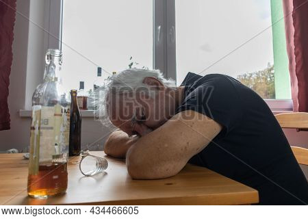 Old Senior Male Man Sit Next To Table Drink Alcohol Bottle At Home Sad Alone Alcoholism Signs And Sy