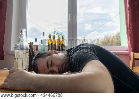 Young Male Man Sit Next To Table Drink Alcohol Bottle At Home Sad Alone Alcoholism Signs And Symptom