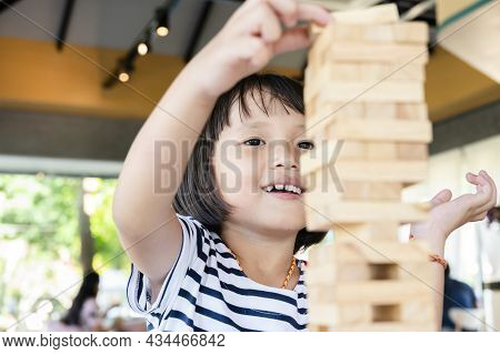 Little Cute Kid Is Playing Jenga Wooden Blocks Game. Having Fun And Learning Creativity
