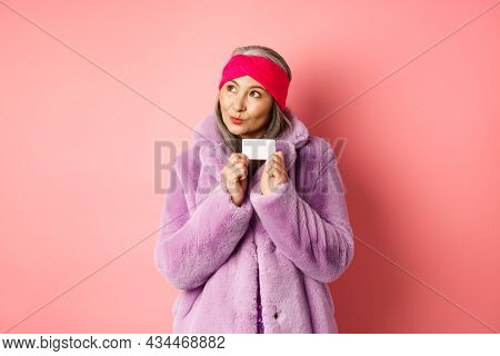 Shopping And Fashion Concept. Fashionable Asian Senior Woman Thinking About Buying Gifts, Holding Cr