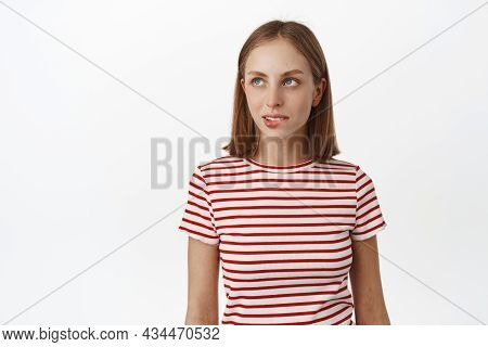 Image Of Thoughtful Blond Girl Wants Something, Biting Lip And Looking Aside With Tempted Look, Has