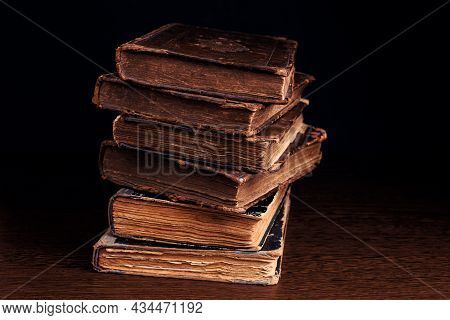 Stack Of Old Worn Shabby Book In Leather Binding On Dark Background. Closeup. Selective Focus