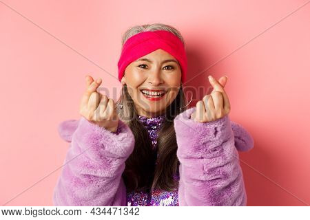 Fashion. Beautiful And Fashionable Asian Senior Woman Smiling, Showing Korean Heart Gesture And Look