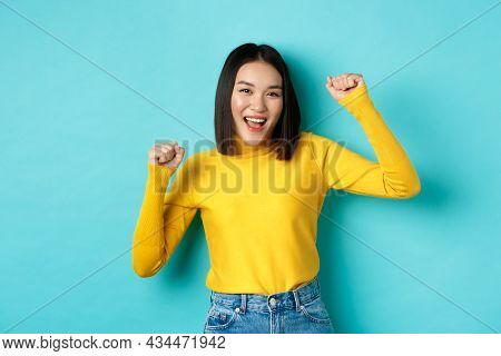 Cheerful Asian Woman Partying, Having Fun And Dancing Over Blue Background, Triumphing And Scream Ye