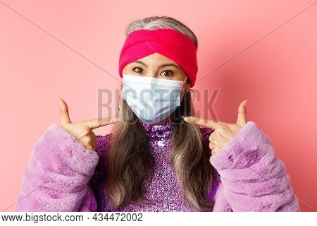 Covid-19, Virus And Fashion Concept. Fashionable Asian Senior Woman In Trendy Outfit Pointing Finger