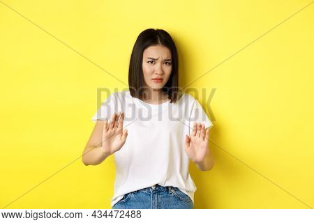 Please No. Asian Woman, Victim Of Assualt Or Domestic Abuse, Pleading With Hands Raised Up In Defens