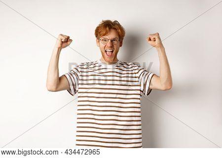 Joyful Redhead Guy Raising Hands Up Like Winner, Winning Prize And Celebrating, Shouting For Joy, St